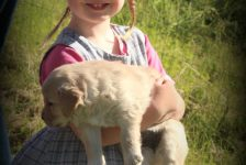 Esther snuggles a puppy while waiting to help administer puppy wormer
